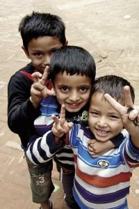 Leikkivät pojat Patanissa lähestyvät turisteja ujostelematta.
