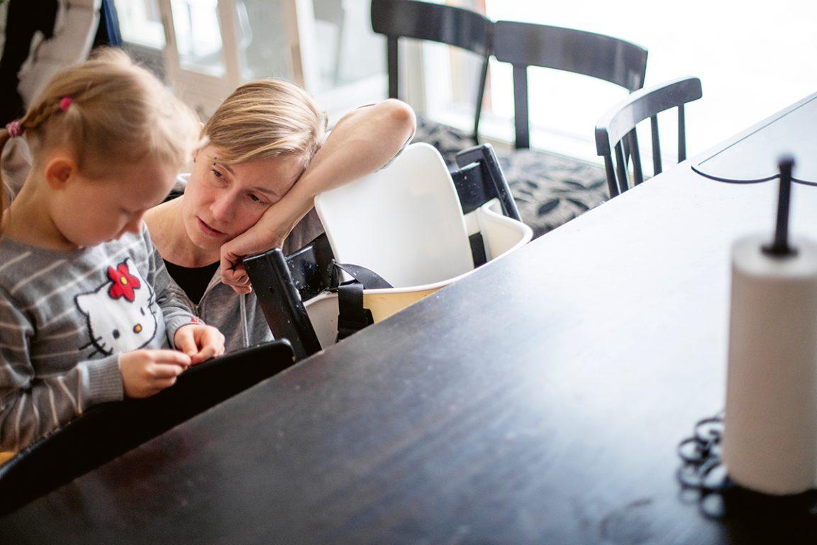 Lapsi istuu pöydän ääressä katsoen alaspäin. Aikuinen on kyykistynyt lapsen viereen ja katsoo lasta myötätuntoisesti.
