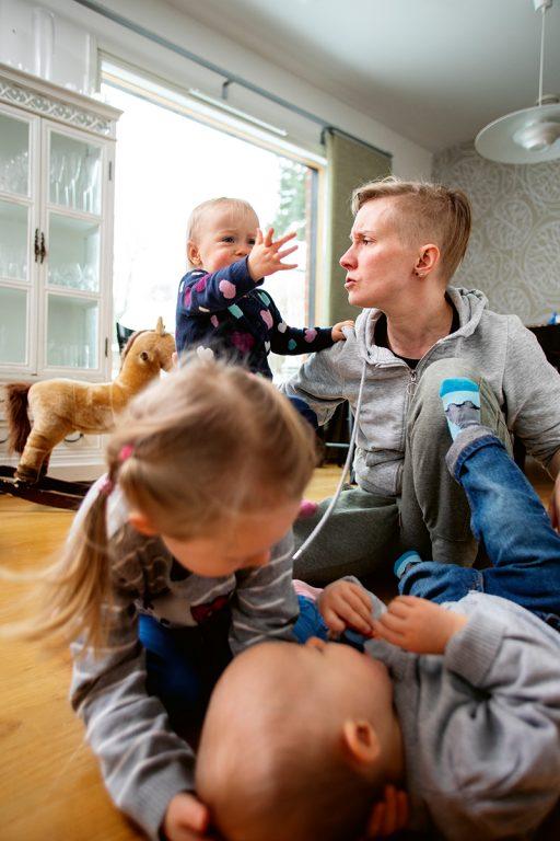 Vanhempi istuu lattialla ja katsoo itkevää taaperoa. Etualalla taapero ja isompi lapsi painivat lattialla.