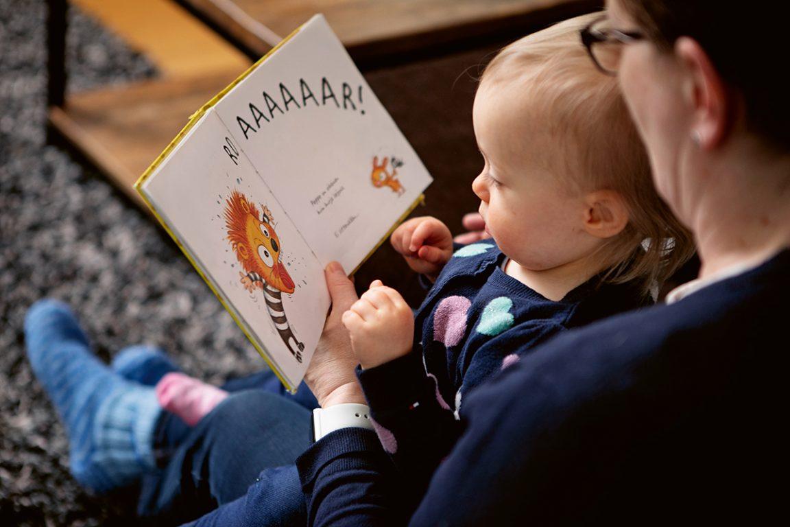 Taapero aikuisen sylissä lukemassa kirjaa.