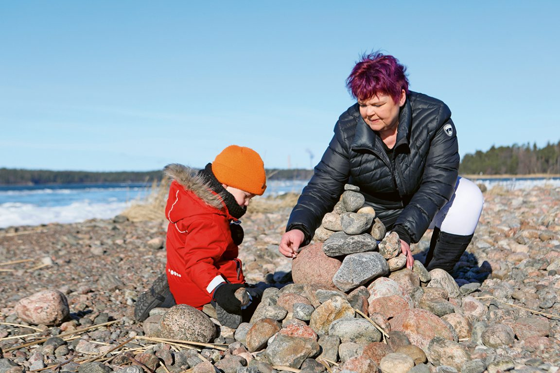 Isoäiti ja lapsenlasi kasaavat rannalla kiviä keoksi. Sininen taivas.