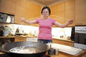 Jieza valmistaa nuudelia näyttävästi. Lopuksi nuudelit tipautetaan mausteliemeen.