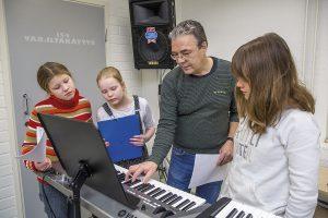 Opettaja Ilari Nieminen näyttää Emma Kostamolle, Joanna Huikurille ja Lila Yletyiselle uuden kappaleen sointukulkua.