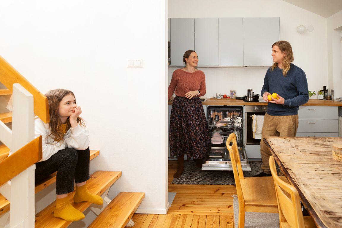 Keittiössä seisovat perheen vanhemmat, portailla istuu perheen lapsi. Etualalla pöytä.