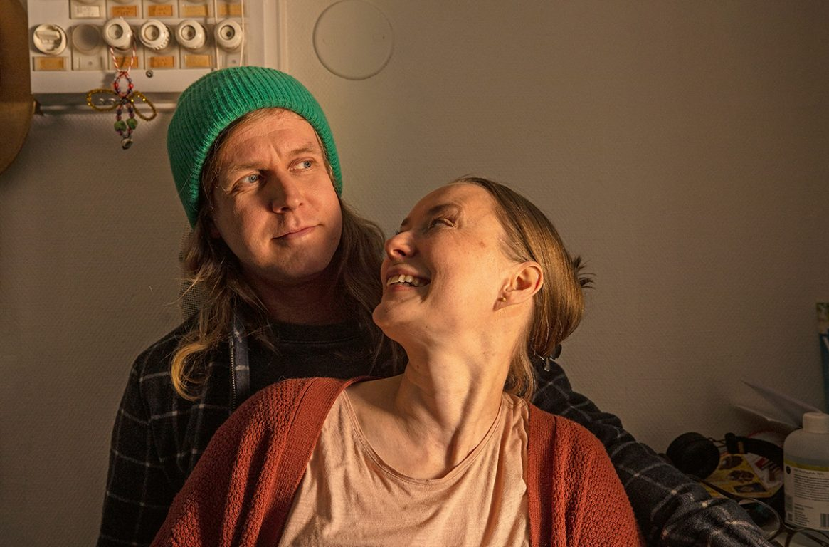 Mikko ja Nea istuvat sylikkäin ja Nea katsoo Mikkoa kohti hymyillen.