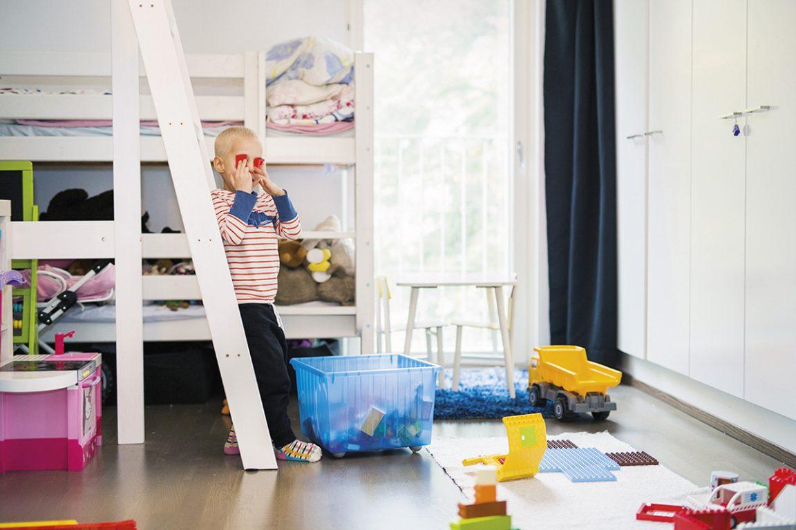 Pieni poika seisoo nojaten kerrosängyn portaisiin.