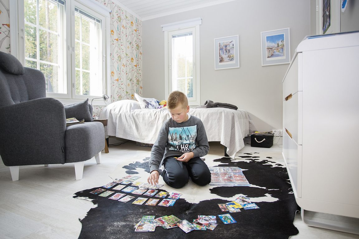 Poika isuu huoneensa lattialla järjestelemässä kortteja.