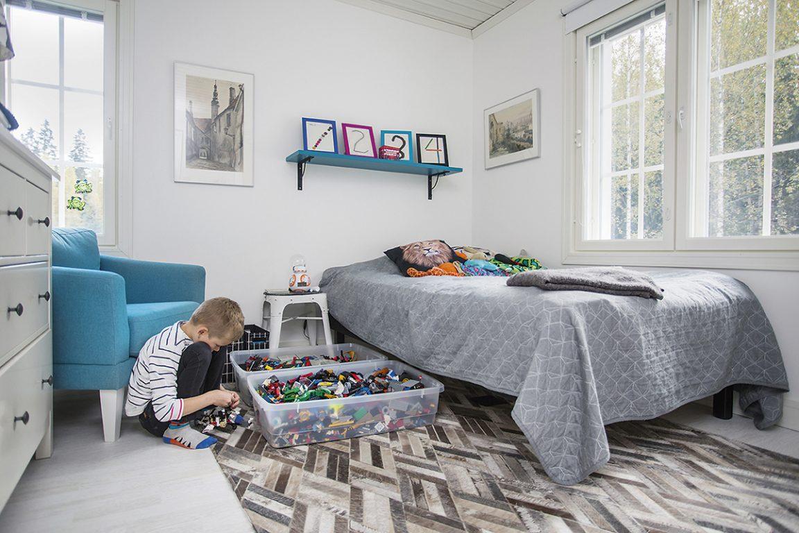 Poika leikkii oman huoneensa lattialla legoilla.