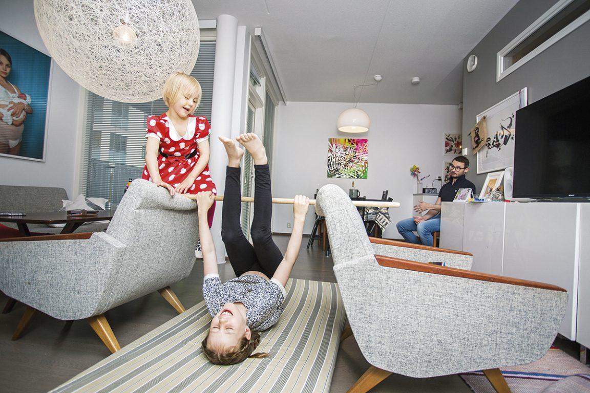 Kaksi lasta leikkivät riehakkaasti sohvalla ja lattialla. Taustalla leikkejä seuraa vanhempi.