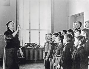 Opettaja on saanut helsinkiläisen kansakoulun pojatkin laulamaan. Kuva Helsingin kaupunginmuseo