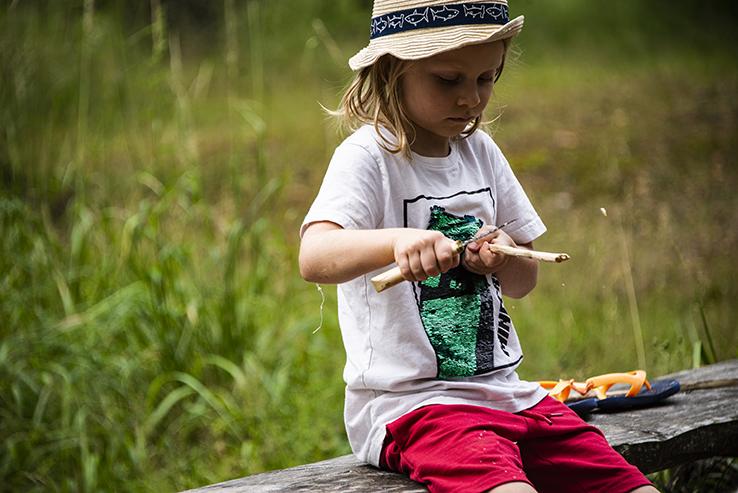 Lapsi veistää puukolla, kesä