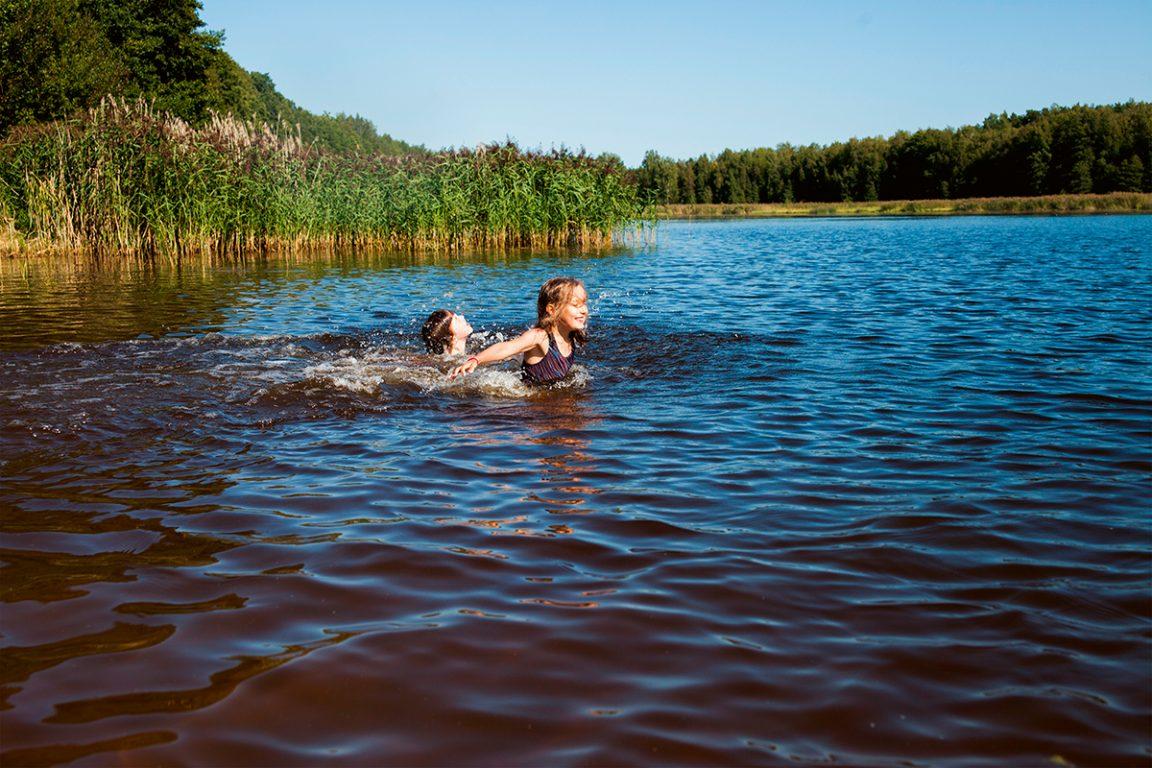 Kaksi tyttöä polskivat iloisesti luonnonvedessä kesällä.
