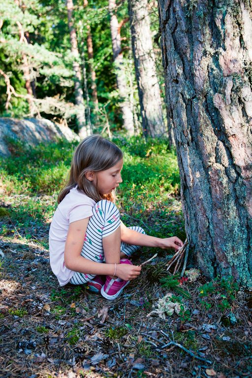 Pieni tyttö rakentaa puun juurelle pientä majaa.