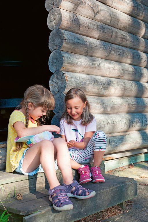 Kaksi tyttöä istuvat puisen kuistin portailla ja tutkivat hymyillen metsästä löytynyttä matoa.