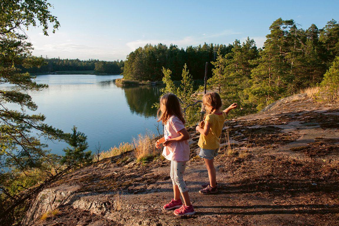 Pienet tytöt heittävät kiviä veteen kalliolta kesäisissä maisemissa.