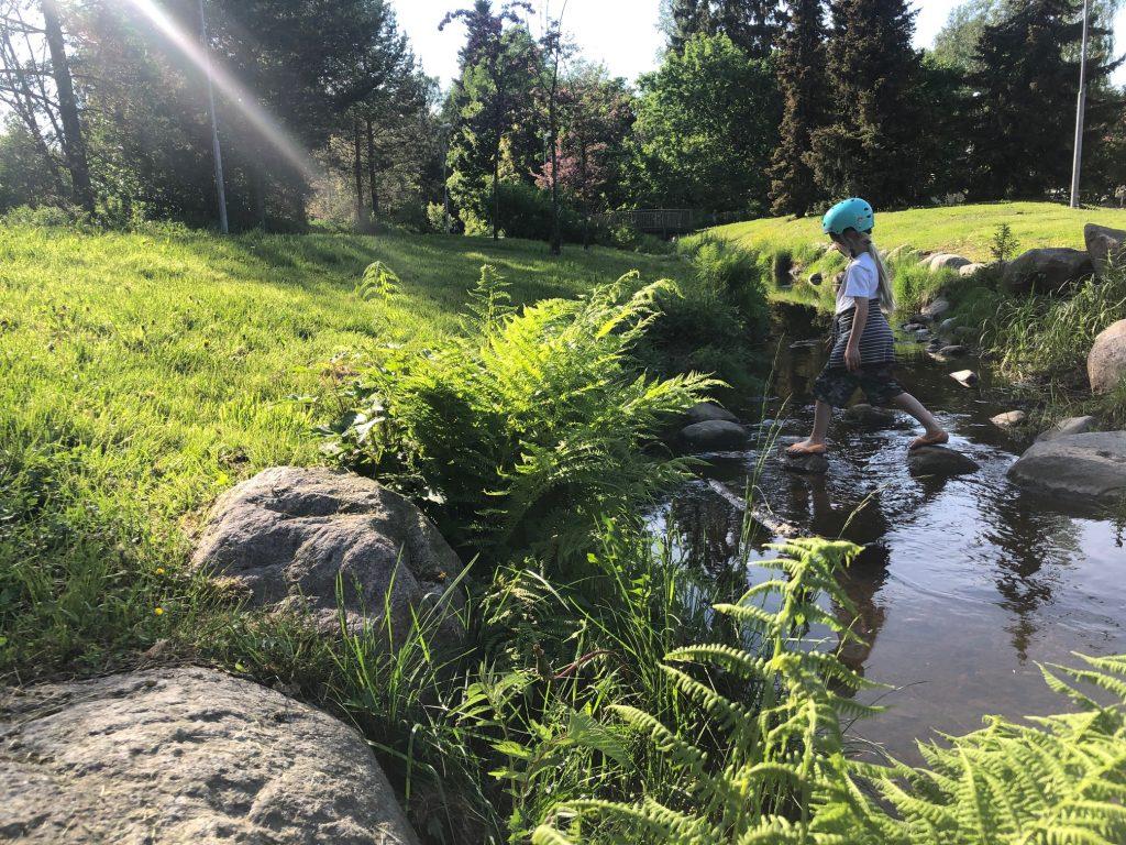 Lapsi ylittää puroa