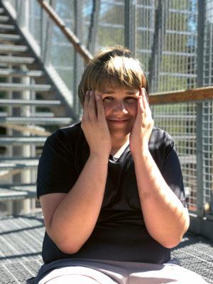 Poikaa istuu portailla. Hän hymyilee kuvaajalle ja pitää kämmeniään reunustamassa kasvojaan.