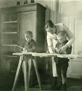 Lastentarhanopettaja opastaa poikia sahaamaan Kotikallion lastentarhassa 1910-luvulla. Kuva Ebeneser-säätiö.