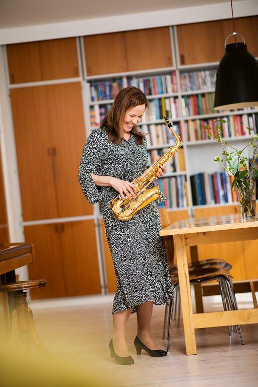 Julia Korkman seisoo kirjahyllyn edessä kädessään alttosaksofoni.