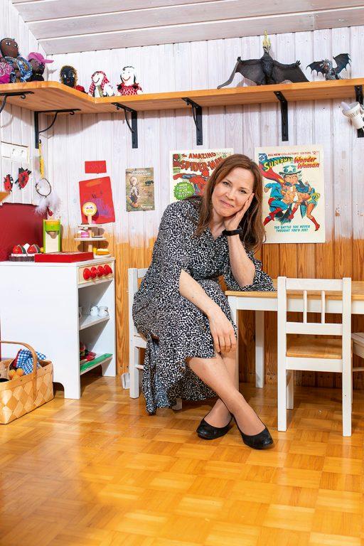 Julia Korkman istuu lastenhuoneen pienen pöydän ääressä lapsen tuolilla. Taustalla hyllyjä, joissa leluja ja lasten tavaroita.