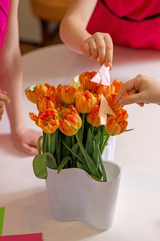 Kukkakimppu, johon lapsen kädet laittavat origamin.