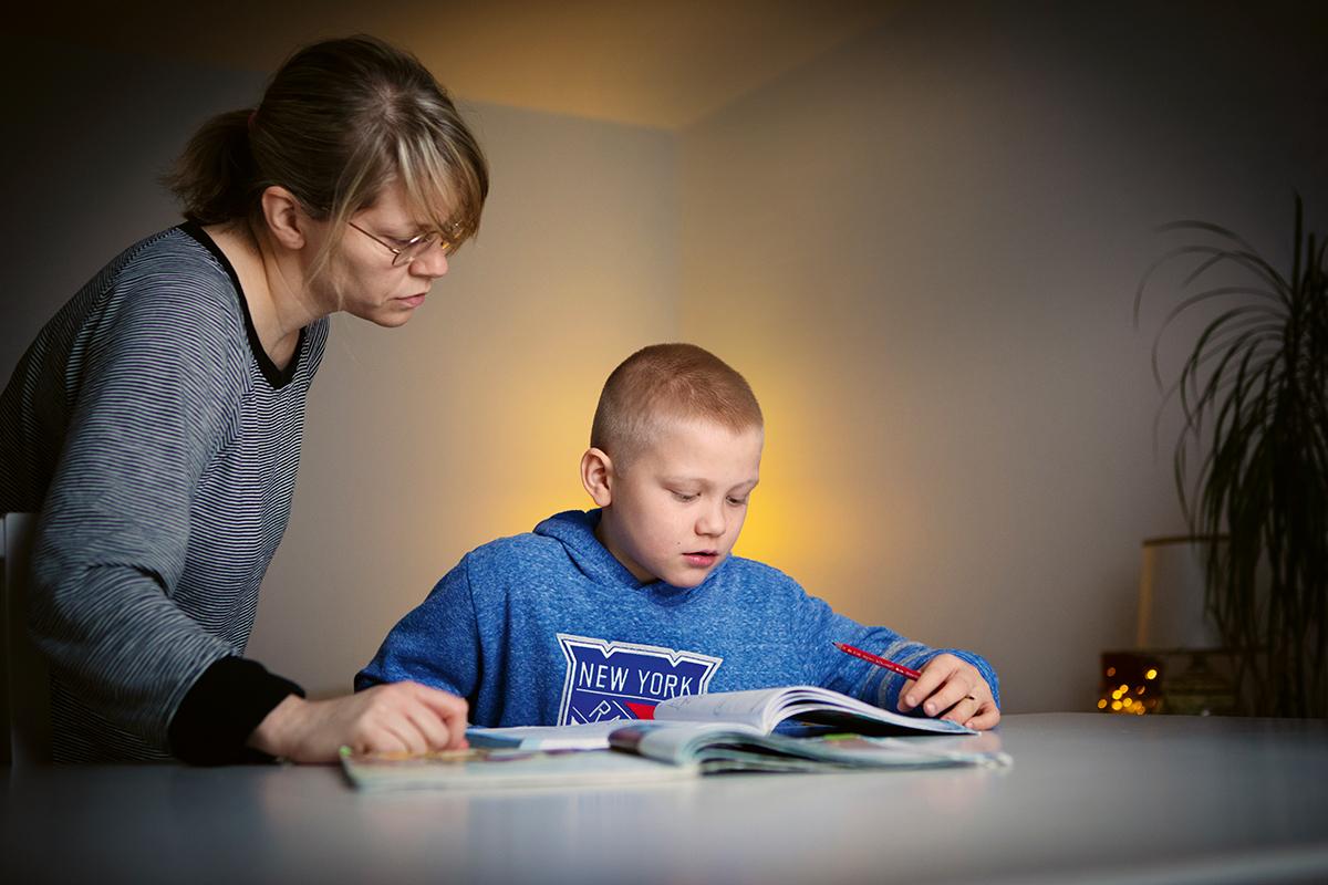 Poika (Jalmari Leino) tekee läksyjä pöydän ääressä. Vieressä pojan äiti seisoo katsoen kirjaa.