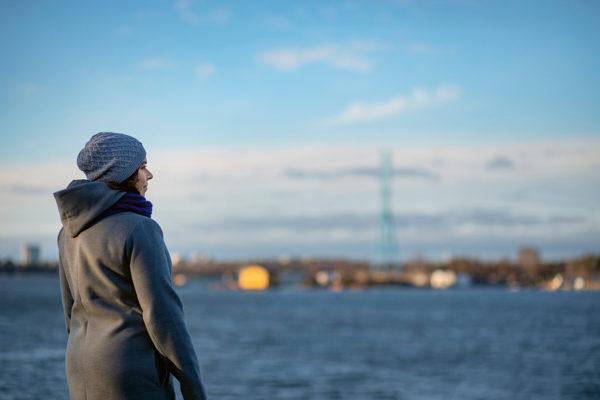 Noora Koponen seisoo katsoen merelle.