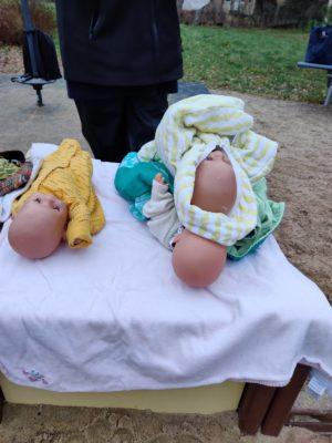 Kolme nukkea puiston pöydällä, kaksi niistä päällekkäin.