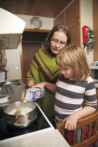 Tukiperheen äiti Sanna Oksanen-Vihervuori auttaa Sannia riisivellin keittämisessä.